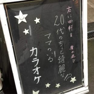 「憧れ遊び」の看板。「右に4軒目。憧れ遊び。20台のちょっと綺麗なママのいるカラオケ」ときれいな時で書かれている。